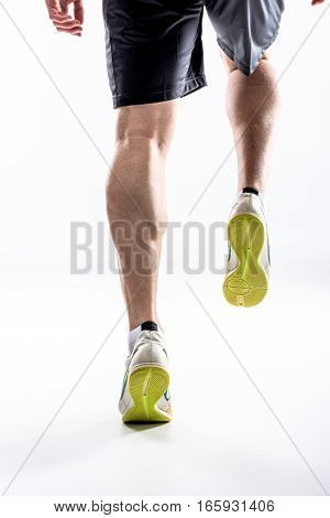 Legs of running man in sneakers on white