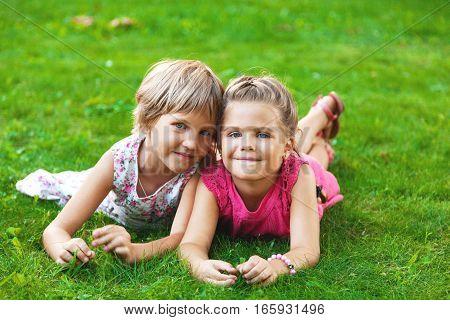 Portrait of Two Little Girlfriends / Sisters Lying Down on Grass