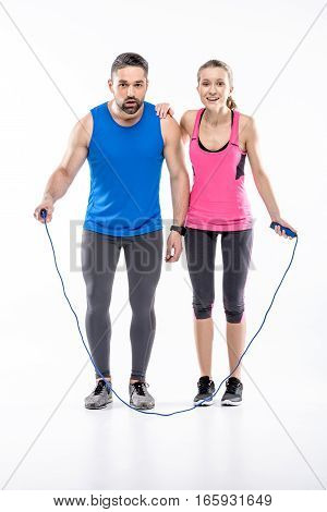 Young sportive couple with skipping rope ready to start workout on white
