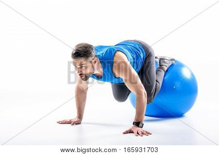 Young man in sportswear doing abs trainting on fit ball on white