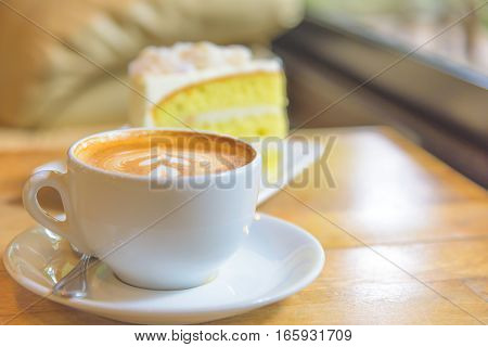 A cup of  coffee and a piece of cake.