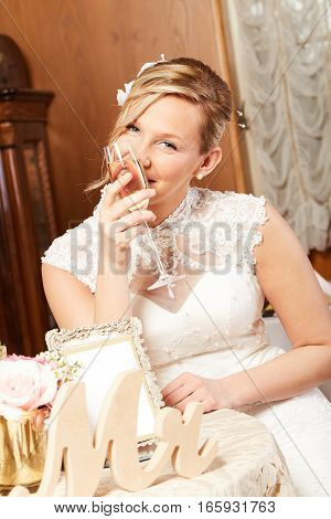 Cheerful bride holding a champagne glass smiling at camera