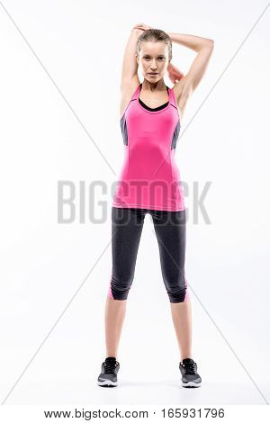 Young woman in sportswear stretching her arms and looking at the camera on white
