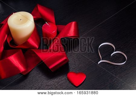 Candles wrapped in red ribbon and hearts on Valentine's Day. Dark texture with a romantic symbol of love.