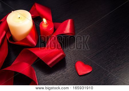 Burning Candle wrapped in a red ribbon and hearts on Valentine's Day. Dark texture with a romantic symbol of love.