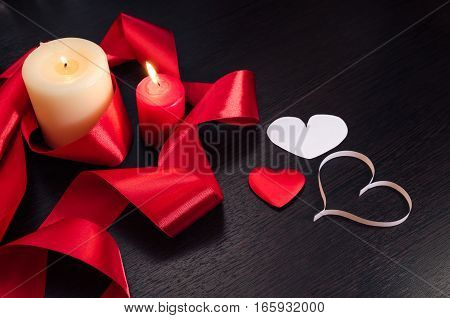 Burning candles, wrapped in red ribbon and hearts on Valentine's Day. Dark texture with a romantic symbol of love by 14 february.