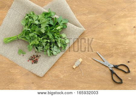 Bunch of parsley is on linen napkin on light brown wooden background. Copy-space composition