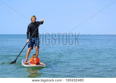 Portrait of a Man and Kid Paddling on Surfboard