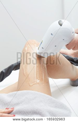 Beautician Giving Epilation Laser Treatment To Woman On legs
