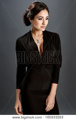 Beautiful woman standing in a black dress over gray background. The woman is not looking at the camera