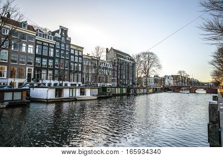 AMSTERDAM NETHERLANDS - JANUARY 10 2017: Famous vintage buildings & chanels of Amsterdam city at sun set. General landscape view. January 10 2017 - Amsterdam - Netherlands.