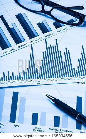 Pen and Eyeglasses on Business Graphs and Charts
