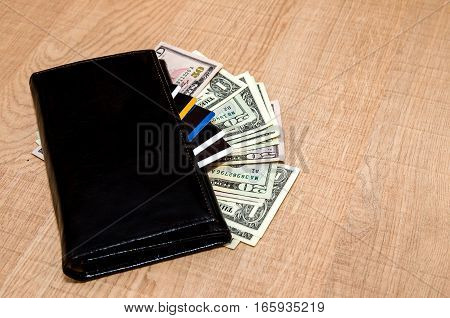 Black Wallet with credit cards and dollar banknotes over table