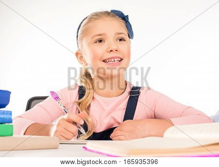 Schoolchild doing homework with happy expression isolated on white