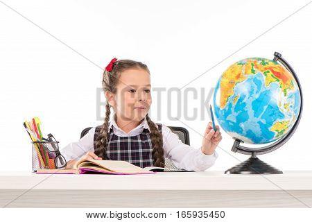 Schoolgirl doing homework and using globe isolated on white