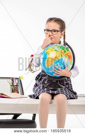 Schoolgirl sitting on table and holding globe on white