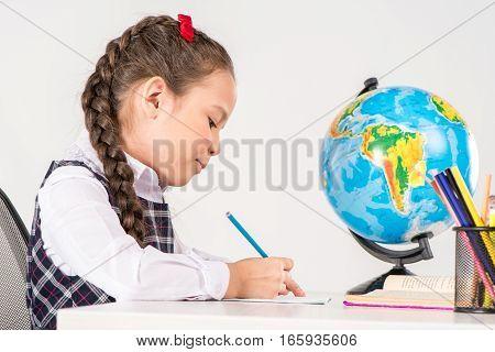 Schoolgirl writing homework with globe behind her on grey