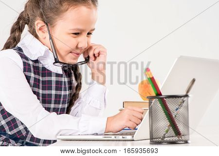 Schoolgirl in glasses sitting at desk with laptop