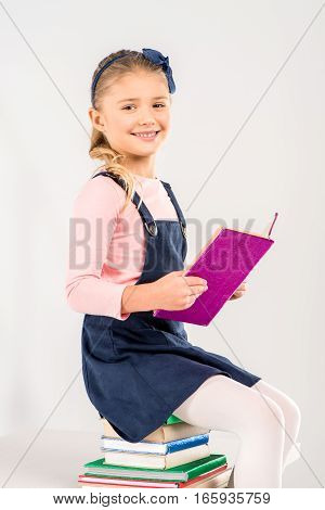 Smiling schoolgirl sitting on pile of books and holding open book on grey