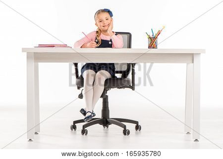Smiling schoolgirl sitting at desk with books and school supplies and looking at camera