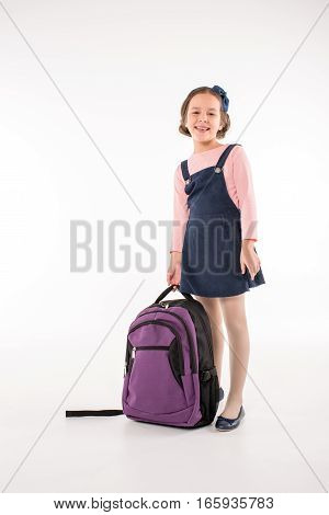 Smiling schoolgirl standing with backpack on grey