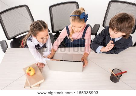 Smiling classmates sitting at desk and using laptop
