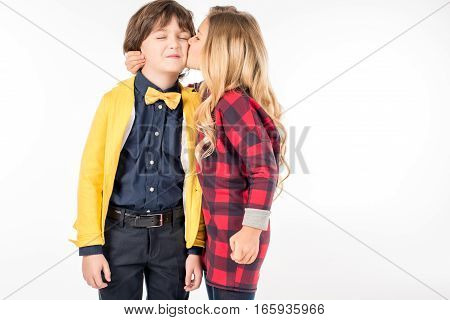 Portrait of schoolgirl hugging and kissing in cheek smiling schoolboy on white