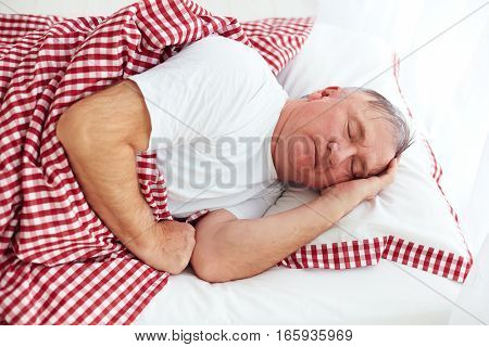 calm mature man sleeps peacefully in bed