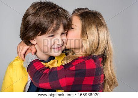 Portrait of schoolgirl hugging and kissing in cheek smiling schoolboy on grey