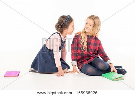 Two schoolgirls sitting with books and talking on white