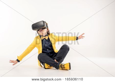 Child in virtual reality headset sitting on grey