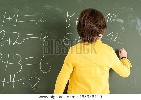 Back view of schoolboy writing with chalk on blackboard