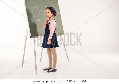 Schoolgirl standing near chalkboard on grey background