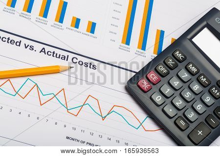Pencil and Calculator on Business Graphs and Charts