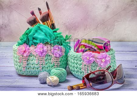 Woven Baskets Decorated With Lace Flowers, Sunglasses, Scarves, Yarn, Makeup Brushes On A Wooden Tab