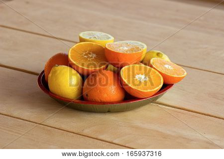 sweet and rip oranges and lemons on a red plate on a wooden table