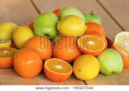 sweet and rip oranges lemons and green apples on a red plate on a wooden table