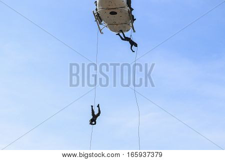Soldier rappelling from helicopter in blue sky with blur propeller