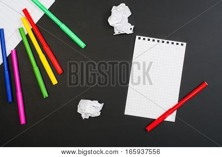 School supplies border on black chalkboard background. Top view product photograph with copy space for text or design. Back to school, education concept