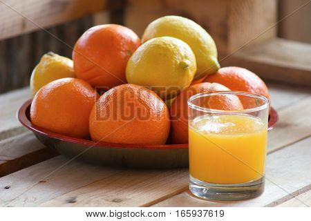 sweet and rip oranges and lemons on a red plate on a wooden table with oranges juice in glass