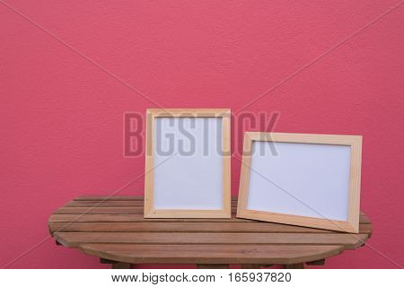 Two photo Frame on a wooden on pink background .