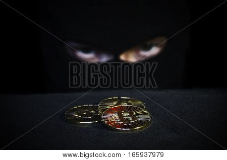 Shiny gold bitcoin coin and masked man face on background