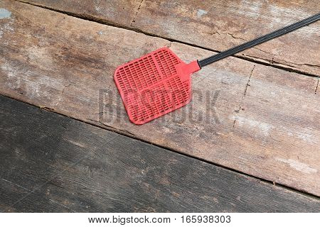 red swatter fly object made of plastic on Wood floor background