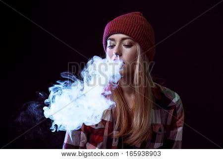 young woman smoking electronic cigarette on black background