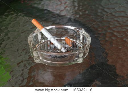 Cigarette in ashtray Placed on table glass