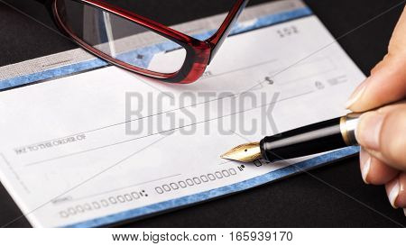 Woman's Hand Writing a Check on Black Background
