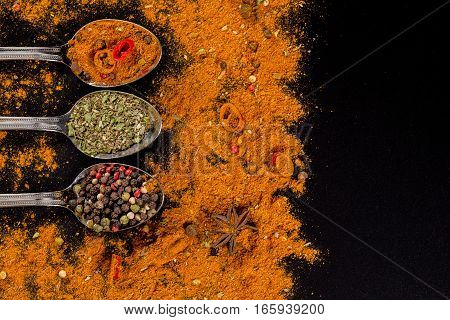 Herbs and spices selection in metal spoons and black background - cooking, healthy eating