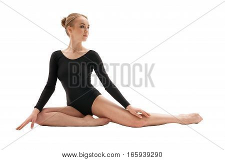 Young blonde girl in black sportsuit sitting gracefully on the floor studio shot