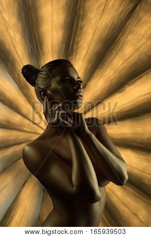 Art fashion photo. Naked sexy model with trendy golden makeup and bodyart posing on studio background