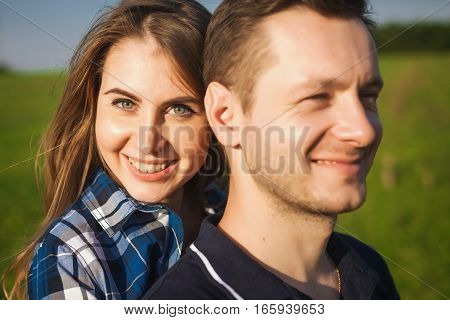 close-up portrait girl in checkered shirt hugging guy from behind in the field